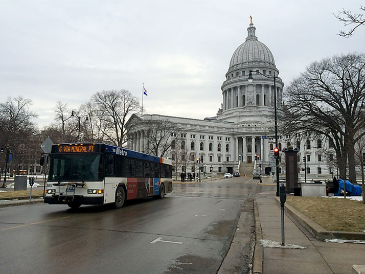 A Madison city bus driving away from the state Capitol in the background